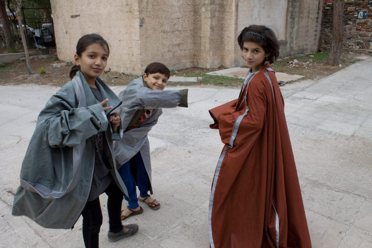 Children in a refugee camp in Greece try on Adiff outerwear